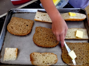 En una charola para hornear, colocar las rebanadas de pan. Untar la mantequilla a cada pieza de pan y por ultimo agregar el azúcar.